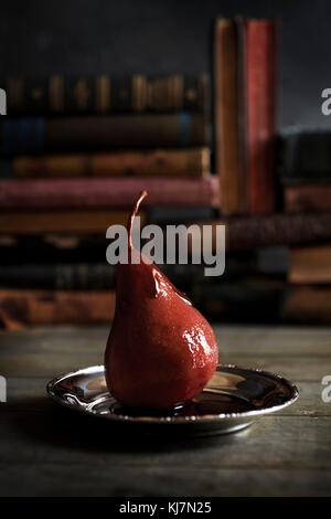 A wine poached pear on silver tray on a table with anitque books in the background. Rustic & moody feel. - Stock Photo