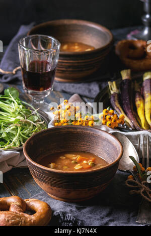 Fall holiday table decoration setting with bowls of hot carrot potato soup, baking pumpkin, carrot, garlic, fresh - Stock Photo