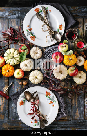Autumn holiday table decoration setting with decorative pumpkins, apples, red leaves, empty plate with vintage cutlery, - Stock Photo