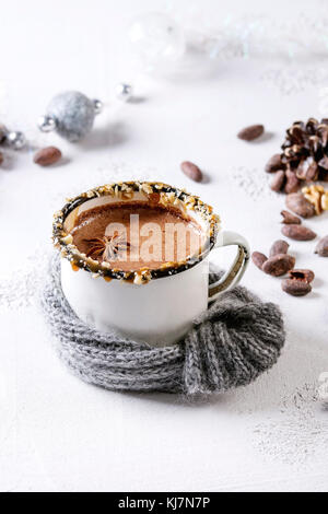 Vintage mug in wool scarf of hot chocolate, decor with nuts, caramel, spices. Ingredients and Christmas toys above - Stock Photo