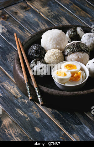Stone tray with different size rice balls with black sesame and seaweed nori, served with soft boiled eggs and chopsticks - Stock Photo