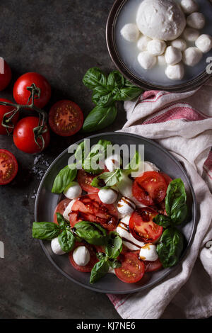 Italian caprese salad with sliced tomatoes, mozzarella cheese, basil, olive oil. Served in vintage metal plate with - Stock Photo