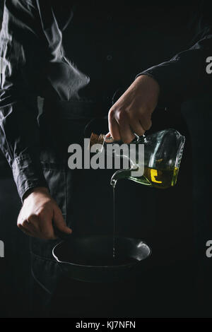 Man chef in black apron pouring olive oil from bottle for cooking pancakes in cast-iron pan. Dark rustic style. - Stock Photo