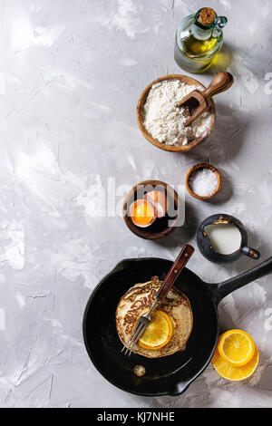 Homemade pancakes with fried orange in cast-iron pan and ingredients above. Wooden bowls of flour, yolk, salt, milk, - Stock Photo