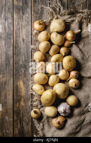 Raw whole washed organic potatoes, onion and garlic on sackcloth over old wooden plank background. Top view with - Stock Photo