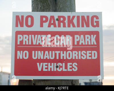 no parking private car park no authorized vehicles sign on post close up; west mersea, essex, england, uk - Stock Photo