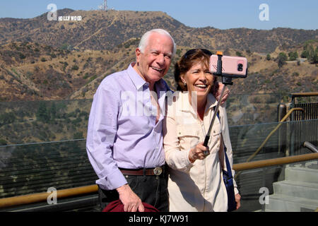 Senior couple with selfie stick taking photo with cell phone camera & Hollywood sign at Griffith Park Observatory - Stock Photo