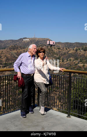 Senior couple holding selfie stick taking cell phone photo in front of Hollywood sign Griffith Park Observatory - Stock Photo