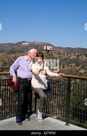 Senior couple taking selfie photograph with cell phone in front of Hollywood sign at Griffith Park Observatory Los - Stock Photo