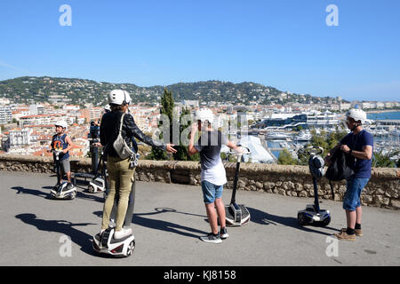 Family Tourists on Segway Scooter Tour in Suquet Old Town of Cannes overlooking La Croisette Waterfront or Seafront, - Stock Photo