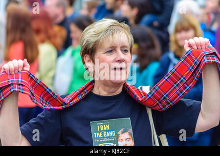 Female performer has tartan scarf and a picture of Alan Longmuir of The Bay City Rollers on her T-shirt enjoying - Stock Photo