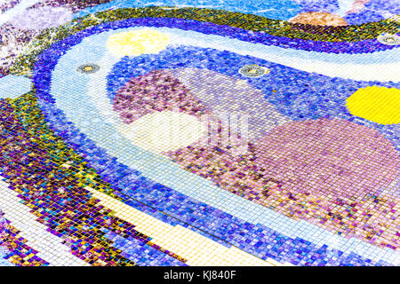 Abstract background of colorful purple, blue, green and yellow tiles mosaic in water fountain - Stock Photo