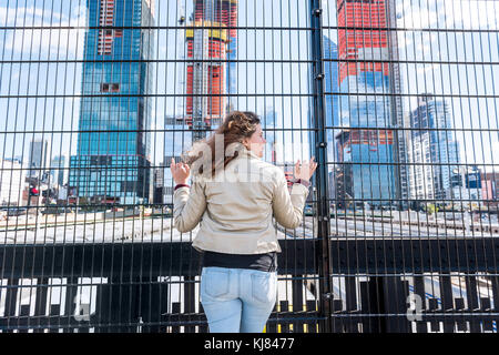 Back closeup of young hipster millennial woman looking at Hudson Yards in NYC New York City Manhattan downtown on - Stock Photo
