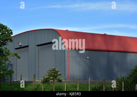 Large barn made from corrugated sheet metal painted gray on walls and red on roof. - Stock Photo