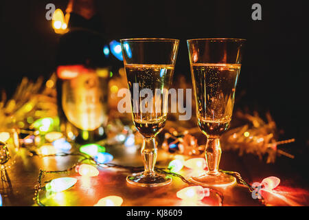 Two sparkling champagne glasses new year celebration christmas festive concept with bottle decorations on wooden - Stock Photo
