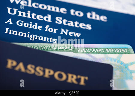 United States of America permanent resident card, green card, displayed with a passport. Immigration concept. Close - Stock Photo