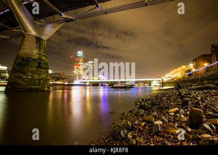 River Thames rocky foreshore under the Norman Foster's millennium bridge looking towards Beetham Tower & Blackfriars - Stock Photo