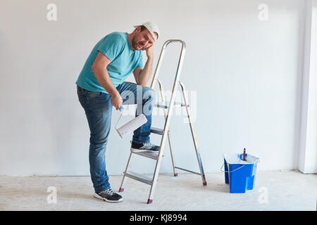 The tired painter rests after painting - Stock Photo