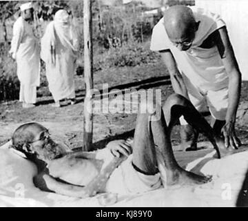 Giving massage, 15 min. daily, to a leper patient, the Sanskrit scholar Parchure Shastri, at Sevagram Ashram, 1940. - Stock Photo