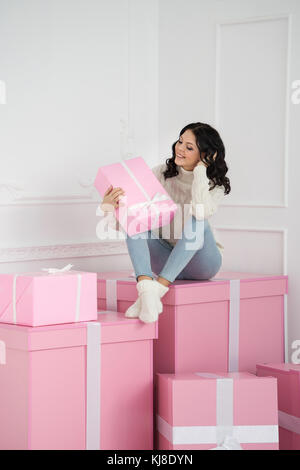 Young cute teenage girl in knitted white sweater and socks. She looks at gift and sits on big pink gift. Holidays. - Stock Photo