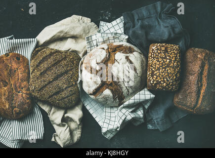 Various bread selection flat-lay, black background - Stock Photo