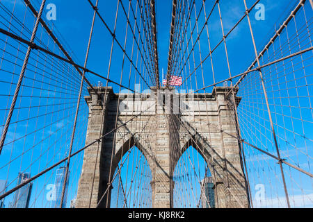 One of the stone towers of the Brooklyn Bridge and an American flag on top - Stock Photo