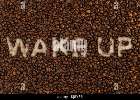 Wake up concept written on coffee beans and jute canvas fabric sack - Stock Photo
