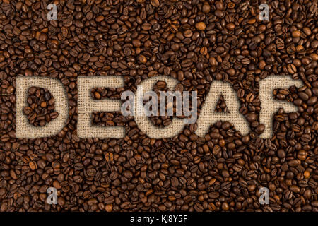 Decaf concept written on coffee beans and jute canvas fabric textile - Stock Photo