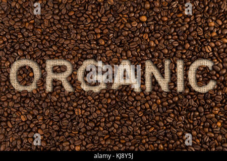 Organic coffee written on roasted beans and jute fabric as bio concept - Stock Photo