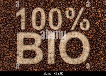 One hundred procent bio coffee concept with roasted beans and text on jute canvas fabric - Stock Photo