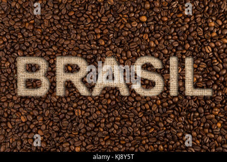 Brasil coffee concept text on roasted beans and jute fabric as high quality country origin - Stock Photo