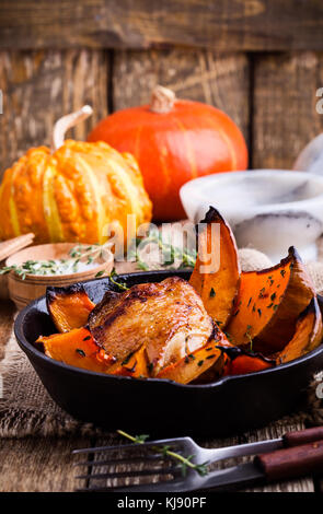 Homemade  Roast chicken thighs with butternut squash and thyme herb in cast iron skillet on rural wooden table - Stock Photo