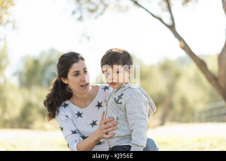 Mother and son in outdoors image in forest. - Stock Photo