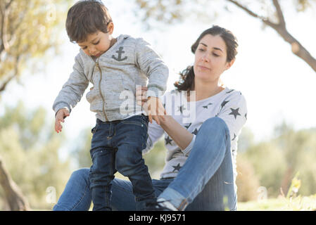 Mother and son in outdoors wood forest park. First steps learning - Stock Photo