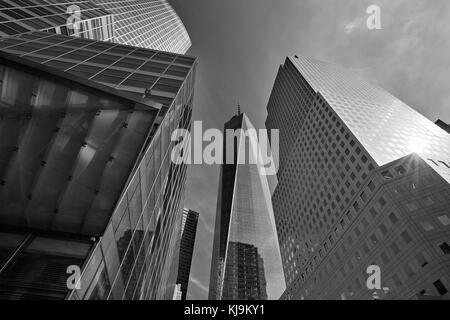 One World Trade Center skyscraper surrounded by glass buildings, black and white and sun beam  in New York - Stock Photo