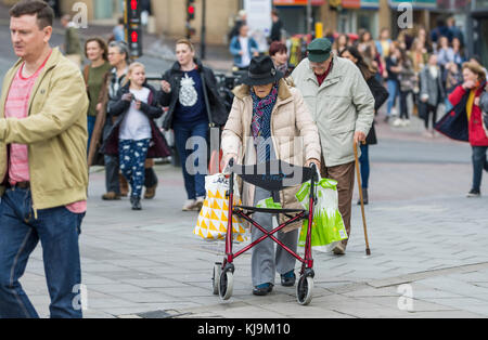 Elderly lady walking through a busy crowded city with the aid of a wheeled Zimmer frame in England, UK. Elderly - Stock Photo
