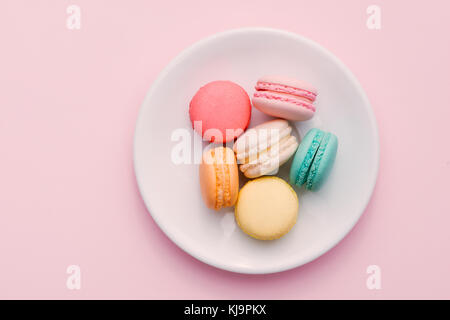 Homemade Colorful macaroons or macaron on White plate - Stock Photo