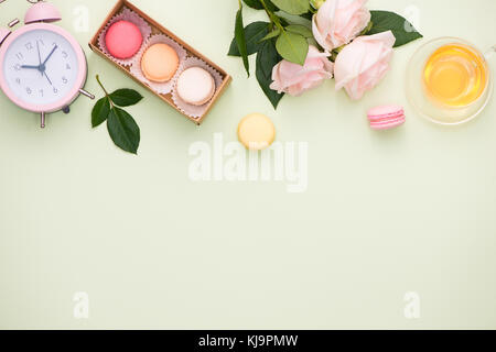 Colorful macaroons and rose flowers with gift box on wooden table. Sweet macarons in gift box. Top view - Stock Photo