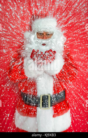 Santa Claus or Father Christmas blowing snow towards you against a red background. - Stock Photo