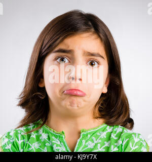 Portrait of a little girl making a sad expression - Stock Photo