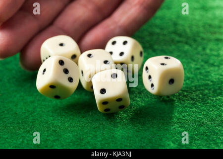 Hand throwing dices on green felt - Stock Photo