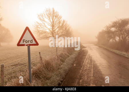 A frosty and icy misty early morning at Ickham as the sun rises, Ice from the ford freezez on the road, Near Canterbury, - Stock Photo