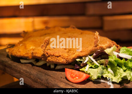 Cachopo, a typical Asturian dish that consists of two large breaded veal fillets filled with ham and cheese - Stock Photo