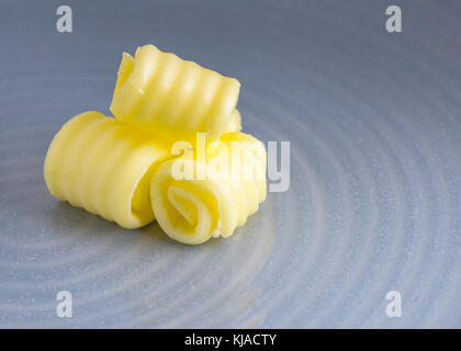 organic butter curled in selective focus, on a plate with blurred background for copy space and text overlay - Stock Photo