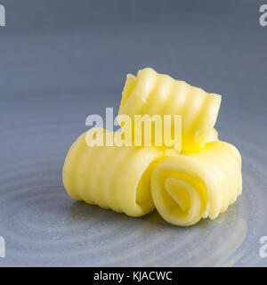 square image of fresh organic butter curled on a plate with space for text overlay and a blue blurred background - Stock Photo