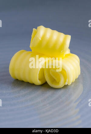 vertical image of fresh organic butter curled on a plate with space for text overlay and a blue blurred background - Stock Photo
