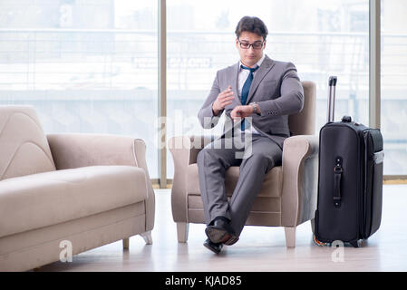 Young businessman in airport business lounge waiting for flight - Stock Photo