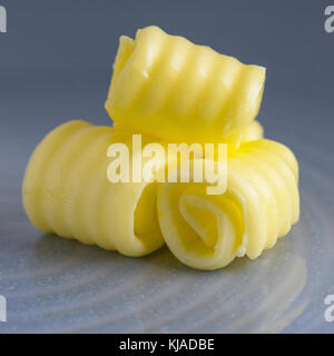square format of fresh organic butter curled on a plate with space for text overlay - Stock Photo