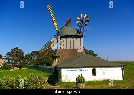 Nebel, Amrum, Germany - June 1st, 2016 - Historic thatched-roof windmill with bright yellow sails and small whitewashed - Stock Photo