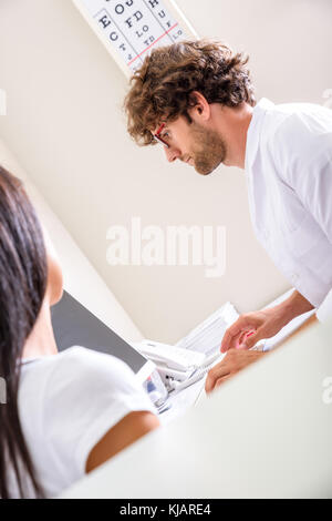 A patient receiving a prescription in the Consultation room from the medic - Stock Photo